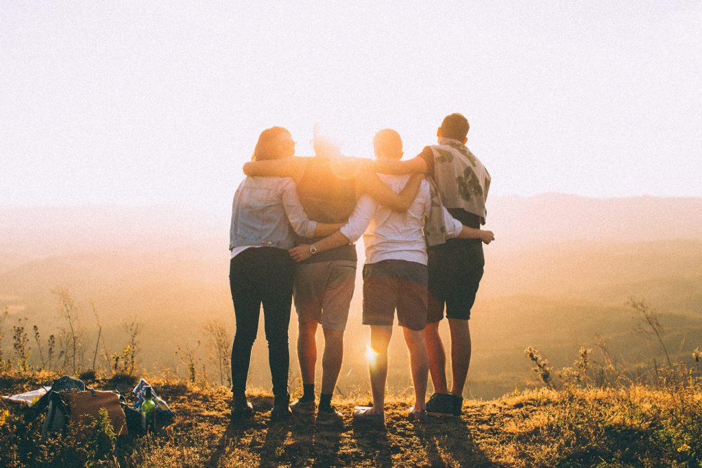 4 ystävystä auringon laskuskun aikaan kalliolla
