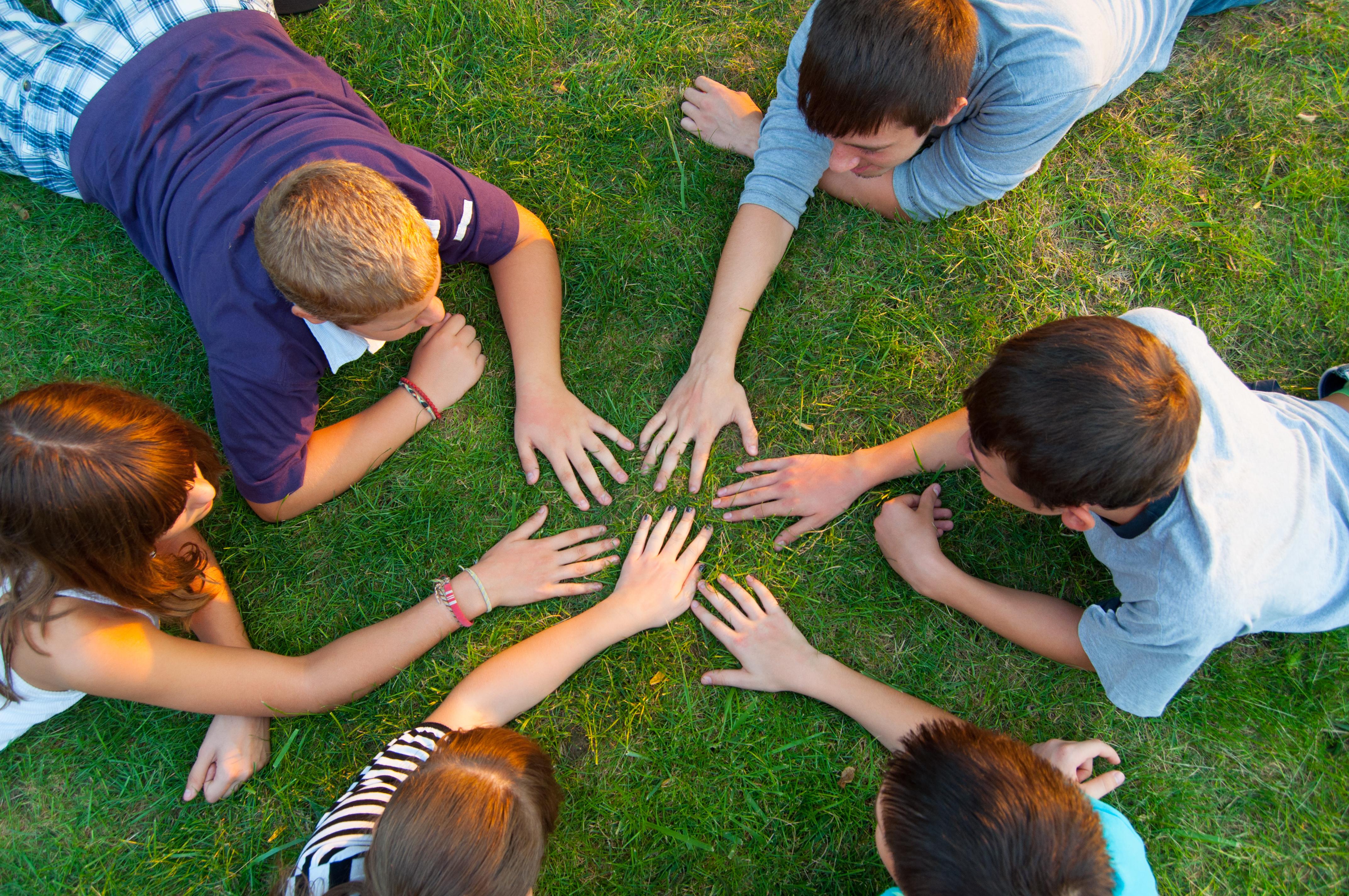 6 nuorta makoilee nurmikolla ringissä. Kaikilla käsi ringin keskellä.