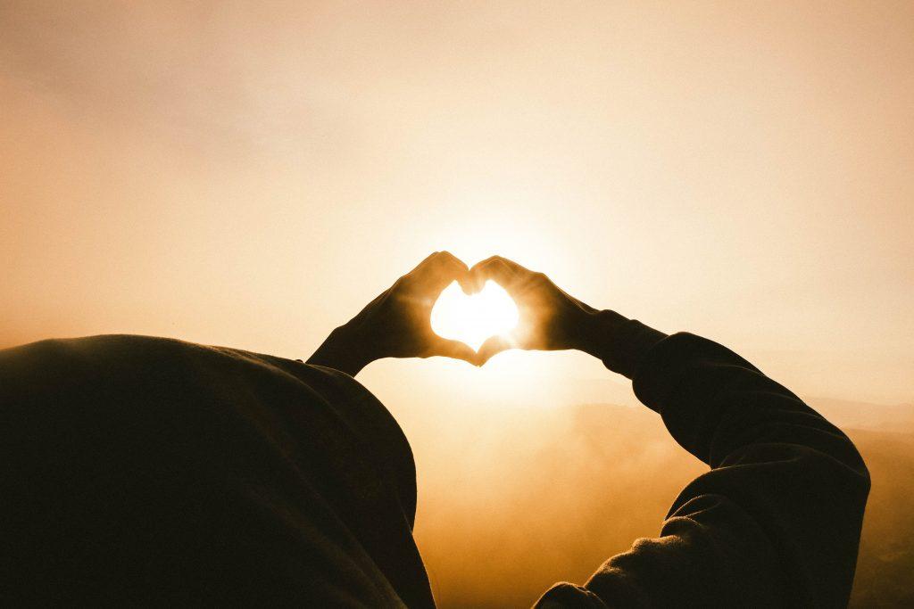 Siluetti aurinkoa vasten heijastuvasta sydämestä, joka on muodostettu käsien väliin.