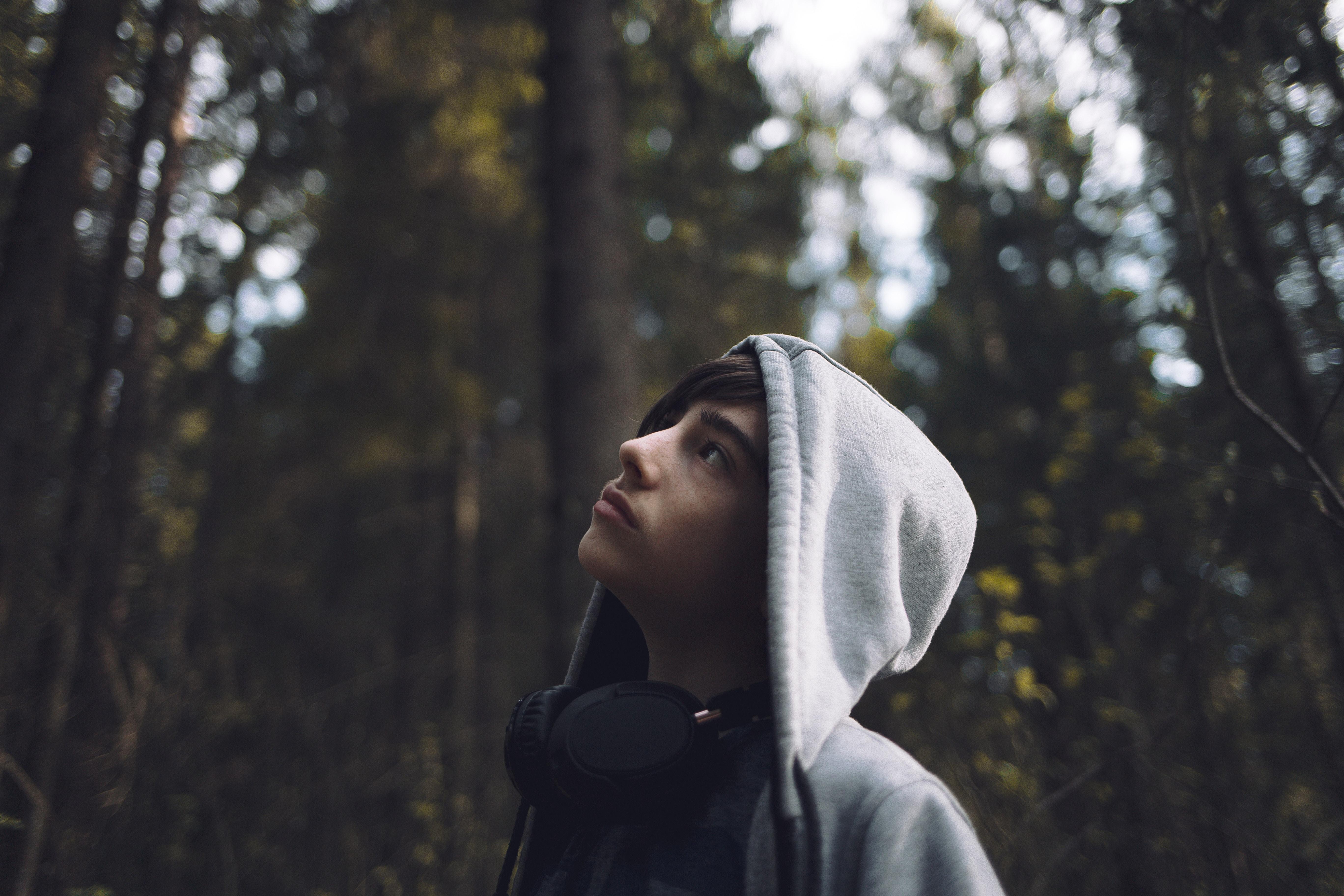 Huppupäinen nuori katsoo taivasta kohti metsämaisemassa.