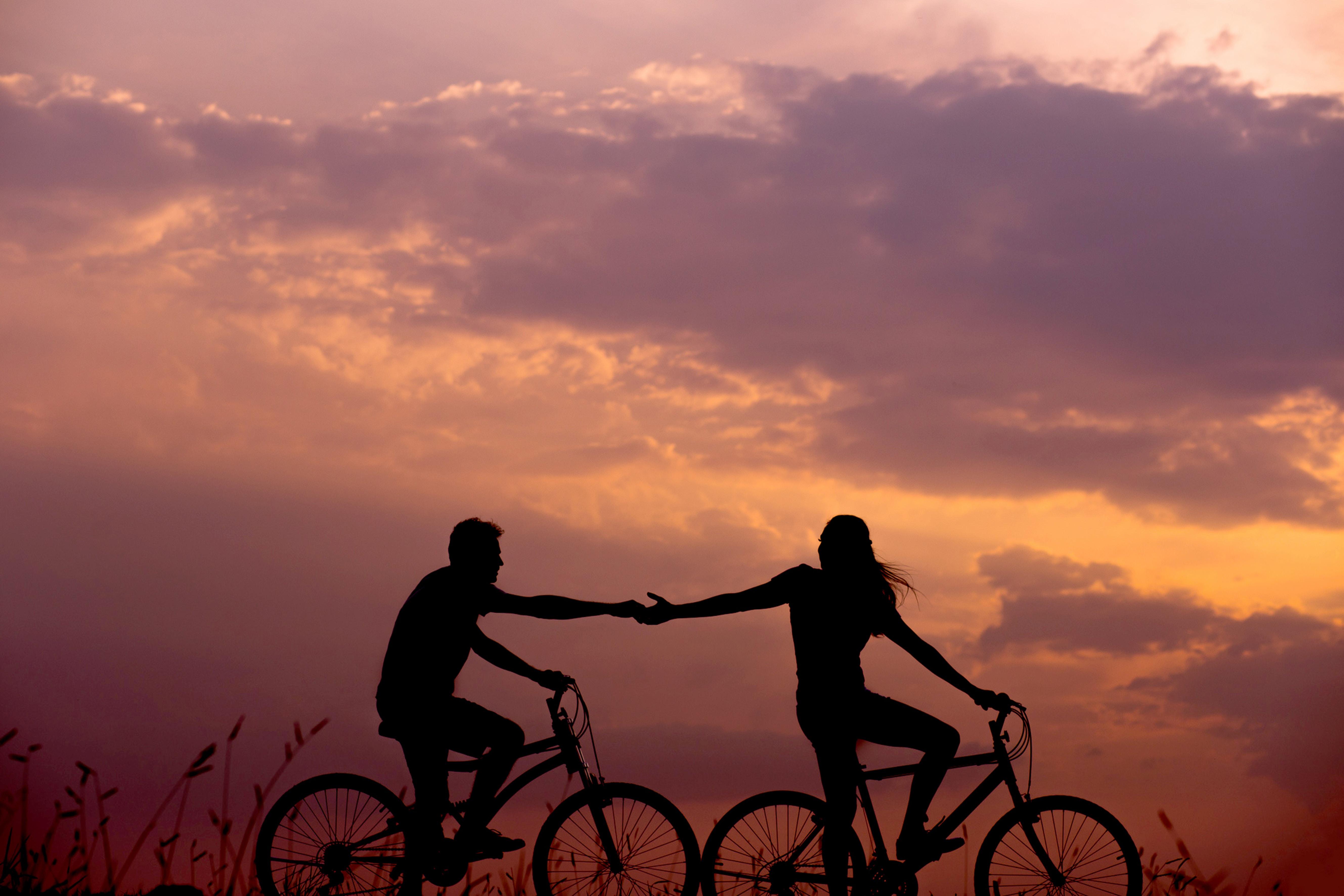 Pyöräilevien nuorten siluetit auringonlaskun värittämää maisemaa vasten. He pitävät toisiaan kädestä.