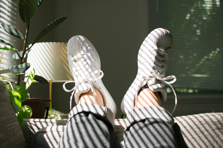 Sohvalla loikoilevan nuoren kenkiin paistaa aurinko sälekaihdinten läpi.