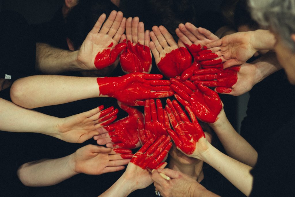 Noin parikymmentä vaaleaa kättä kurkottavat toisiinsa ja käsiin on piirretty punainen sydän-kuvio.